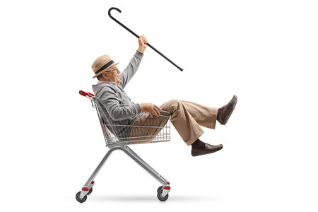 Cheerful mature man with a cane riding inside a shopping cart isolated on white background Stock Photo