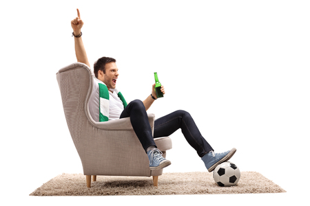 Excited football fan with a scarf and a beer bottle seated in an armchair pointing up with his finger isolated on white background Foto de archivo