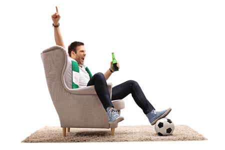 Tifoso emozionante con una sciarpa e una bottiglia di birra messe in una poltrona che indica su con il suo dito isolato su fondo bianco Archivio Fotografico - 90263737