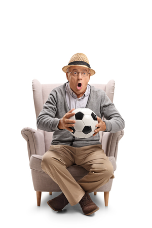 Excited mature man holding a football and sitting in an armchair isolated on white background