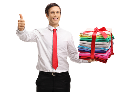Formally dressed man with a stack of ironed and packed clothes wrapped with red ribbon as a present making a thumb up gesture isolated on white background