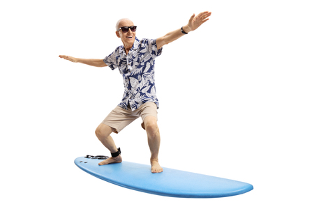 Joyful elderly man surfing isolated on white background Foto de archivo