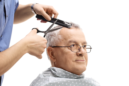 Mature man having a haircut isolated on white background