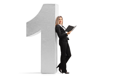 Full length profile shot of a formally dressed woman with a book leaning against a cardboard number one isolated on white background