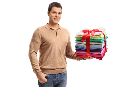 Guy holding a stack of ironed and packed clothes wrapped with red ribbon as a present isolated on white background Stock Photo