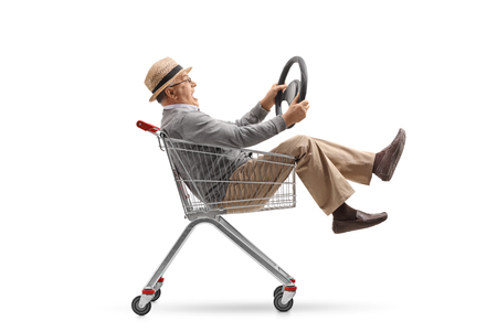 Mature man with a steering wheel riding inside a shopping cart isolated on white background