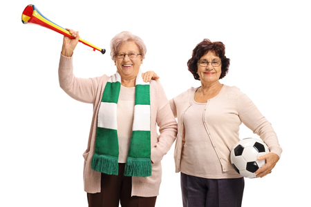 Elderly soccer fans with a football and a trumpet isolated on white background