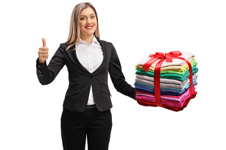 Formally dressed woman with a stack of packed and ironed clothes wrapped with red ribbon as a gift making a thumb up sign isolated on white background