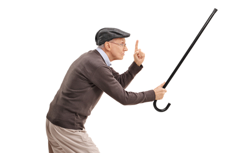 Angry senior holding his cane as a sword and gesturing with his finger isolated on white background Stock Photo