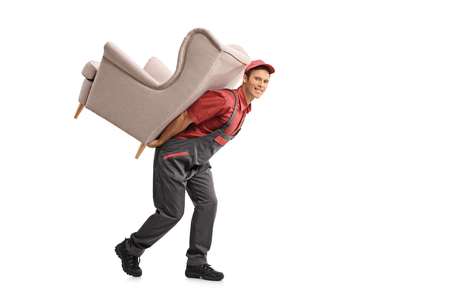 Full length portrait of a serviceman carrying an armchair on his back isolated on white background Stock Photo