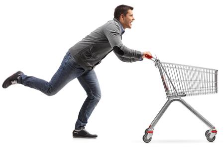 Profilaufnahme in voller Länge eines Kerls, der einen leeren Warenkorb lokalisiert auf weißem Hintergrund laufen lässt und drückt Standard-Bild