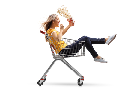 Young woman with a box of popcorn riding inside a shopping cart isolated on white background