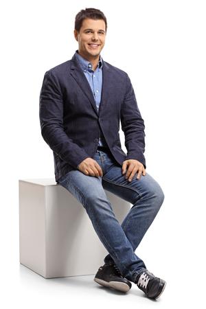Elegant guy sitting on a cube isolated on white background