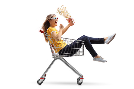 Young woman with a popcorn box and 3D glasses riding inside a shopping cart isolated on white background