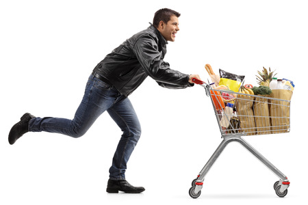 Full length profile shot of a biker running and pushing a shopping cart filled with groceries isolated on white background Foto de archivo