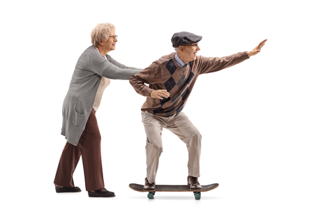 Full length profile shot of an elderly woman pushing an elderly man on a skateboard isolated on white background Stock Photo