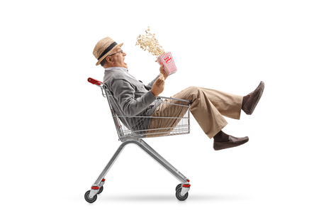 Excited mature man with a box of popcorn riding inside a shopping cart isolated on white background Stock Photo
