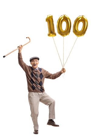 Full length portrait of an overjoyed senior with a cane and a golden number hundred balloon isolated on white background