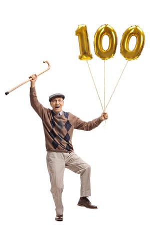 Portrait de toute la longueur d'un senior ravi avec une canne et un ballon d'or nombre cent isolé sur fond blanc