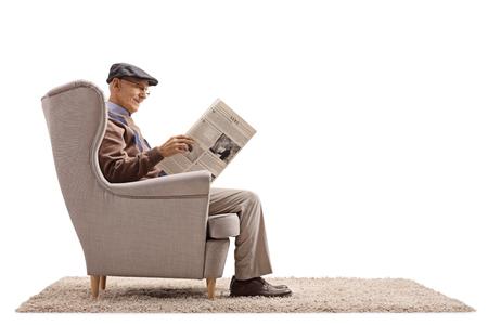 Oudste gezet in een leunstoel die een krant lezen die op witte achtergrond wordt geïsoleerd