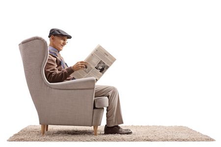 Senior seated in an armchair reading a newspaper isolated on white background