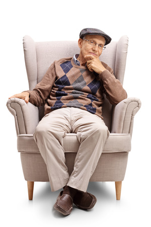 Senior sitting in an armchair and looking away isolated on white background