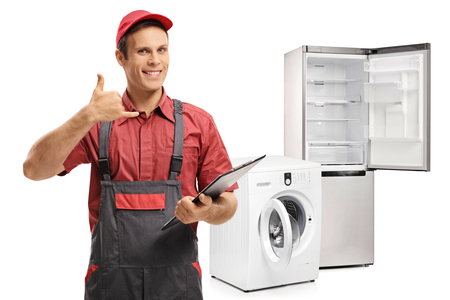 Repairman with a clipboard making a call me gesture in front of a washing machine and a fridge isolated on white background