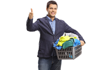 Elegant man with a laundry basket full of clothes making a thumb up gesture isolated on white background Stock Photo