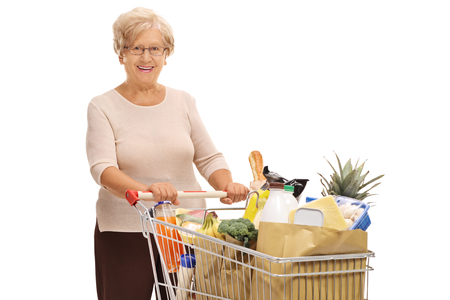 Elderly woman with a shopping cart full of groceries isolated on white background