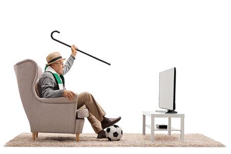 Aficionado fanático del fútbol anciano con una bufanda y un bastón sentado en un sillón viendo televisión aislado sobre fondo blanco Foto de archivo - 91827244
