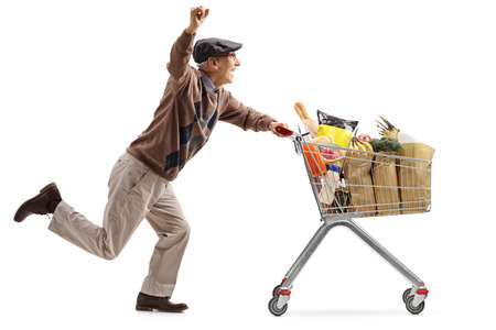Joyful elderly man pushing a shopping cart filled with groceries and holding his hand up isolated on white background Stock Photo