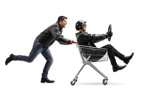 Biker pushing a shopping cart with another biker holding a steering wheel and riding inside isolated on white background Stock Photo
