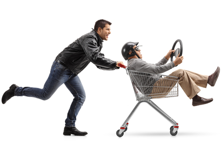 Biker pushing a shopping cart with a mature man with a helmet and a steering wheel riding inside isolated on white background