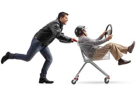 Motorista empujando un carrito de compras con un hombre maduro con un casco y un volante dentro de montar aislado sobre fondo blanco