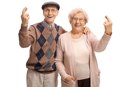 Elderly couple holding their fingers crossed isolated on white background