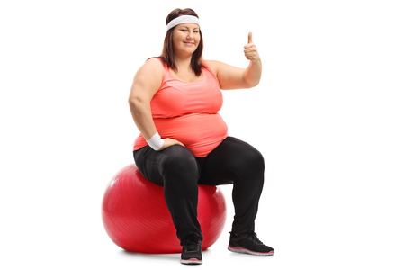 Overweight woman sitting on a pilates ball and making a thumb up sign isolated on white background Stock Photo