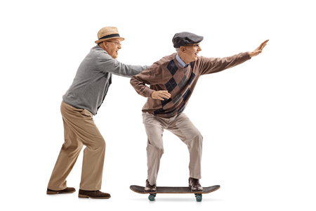 Full length profile shot of a senior pushing another senior on a skateboard isolated on white background Stock Photo