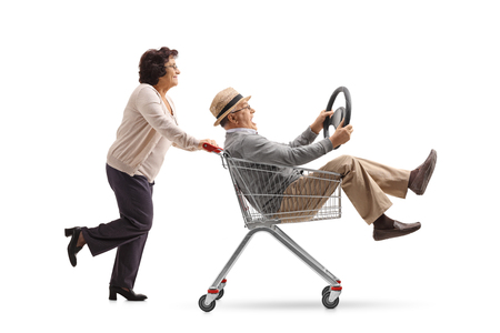 Mature woman pushing a shopping cart with a mature man with a steering wheel riding inside isolated on white background