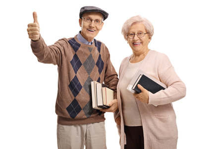 Seniors with books making a thumb up gesture isolated on white background