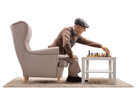 Senior seated in an armchair playing a game of chess with himself isolated on white background