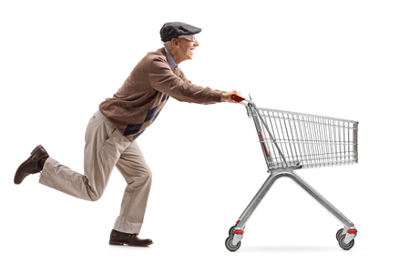Full length profile shot of a senior with 3D glasses running and pushing an empty shopping cart isolated on white background Stock Photo