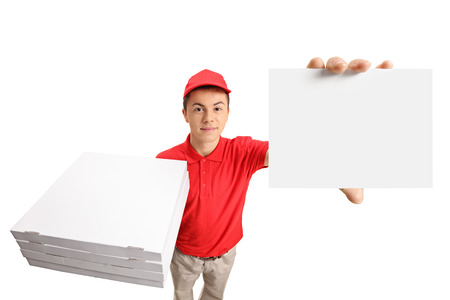 Teenage pizza delivery boy with a stack of pizza boxes and a blank card isolated on white background