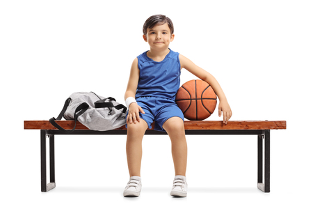 Little basketball player sitting on a wooden bench next to a sports bag isolated on white background Stock Photo