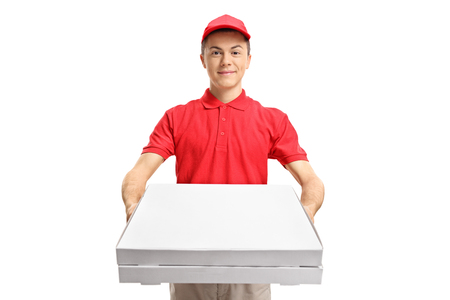 Teenage pizza delivery boy giving pizza boxes isolated on white background Фото со стока