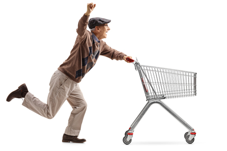 Full length profile shot of a joyful senior pushing an empty shopping cart and holding his hand up isolated on white background
