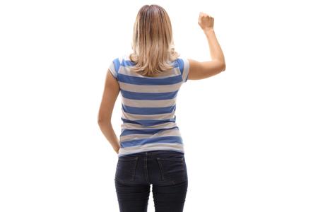 Jonge vrouw die op een deur kloppen die op witte achtergrond wordt geïsoleerd