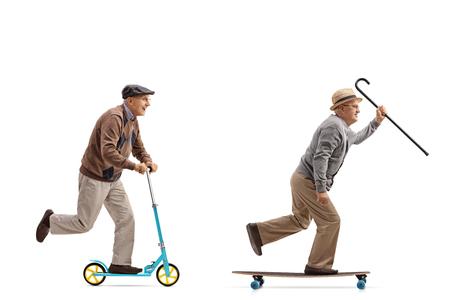 Het volledige schot van het lengteprofiel van twee bejaarden met één van hen die een autoped berijden en andere die een longboard berijden op witte achtergrond wordt geïsoleerd