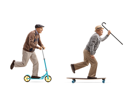 Full length profile shot of two elderly men with one of them riding a scooter and the other riding a longboard isolated on white background