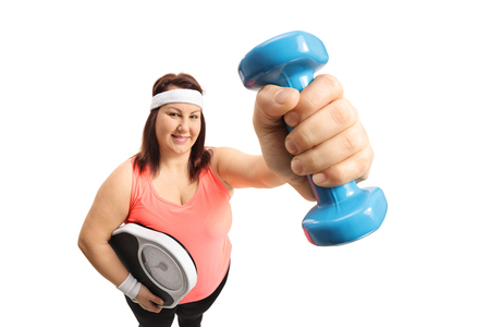 Overweight woman holding a weight scale and a dumbbell isolated on white background
