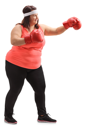 Full length profile shot of an overweight woman with boxing gloves isolated on white background